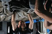 picture of auto repair shop  - Auto mechanics working under the car  - JPG