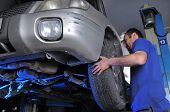 stock photo of car repair shop  - Car mechanic changing flat tire  - JPG