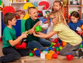 Children building blocks in kindergarten. Group boys and girls playing toy on floor . Interior presc poster
