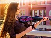 Playing viola woman perform music on violin in park outdoor. Girl performing jazz on city street . S poster