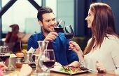 leisure, eating, food and drinks, people and holidays concept - smiling couple having dinner and dri poster