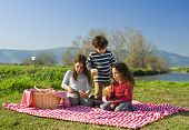 Three kids eating sandwiches at a picnic