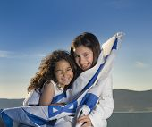 stock photo of israeli flag  - two girls holding hugging the Israeli flag - JPG