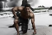 foto of young men  - Dark stylized portrait of a young muscular shirtless man on the beach with storm and crashing waves in background - JPG