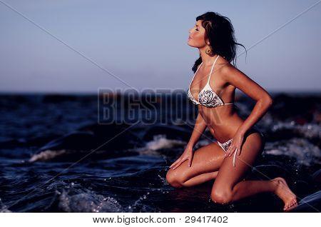Woman In Bikini Kneeling On Rock
