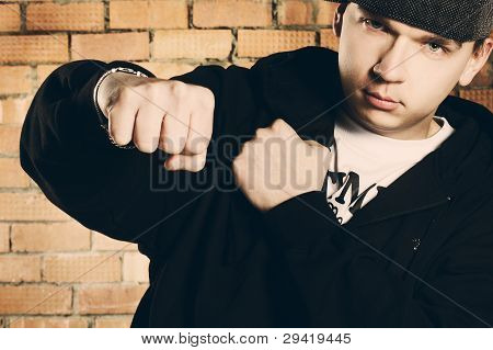Portrait Of Serious Hip-hop Man Fighting Before Brick Wall