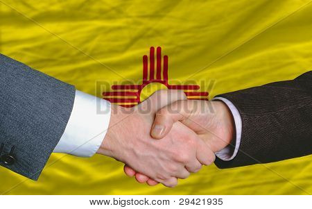 In Front Of American State Flag Of New Mexico Two Businessmen Handshake After Good Deal