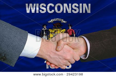 In Front Of American State Flag Of Wisconsin Two Businessmen Handshake After Good Deal