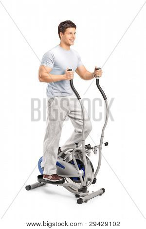 Handsome man exercising on a cross trainer machine, isolated on white
