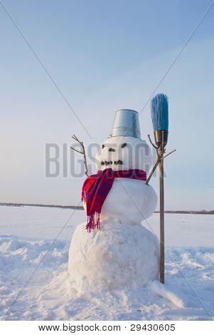 Boneco de neve solitário em um campo nevado