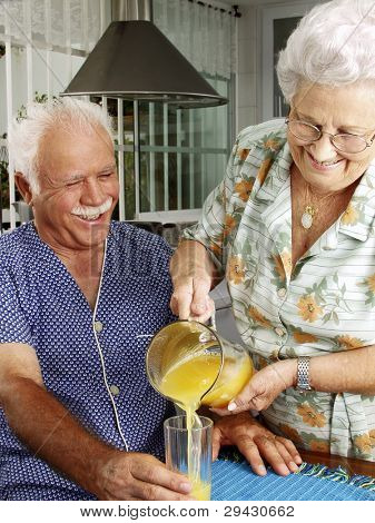 Grand parents drinking and pouring orange juice at kitchen.