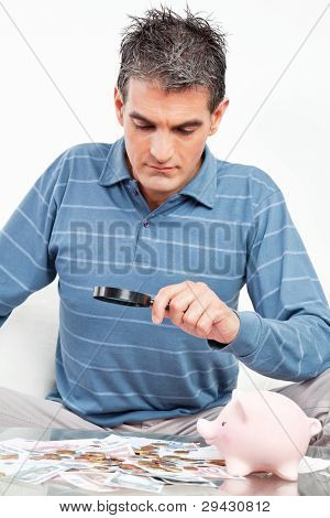 Man with money and piggy bank looking through magnifying glass
