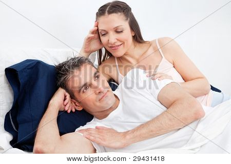 Homem infeliz na cama a afastar mulher sedutora