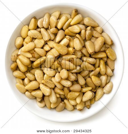 Pine nuts in small bowl, isolated on white background.  Overhead view.
