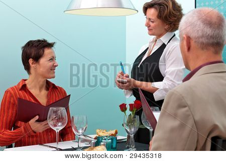 Photo of a waitress taking a food order from a mature couple dining in a restaurant