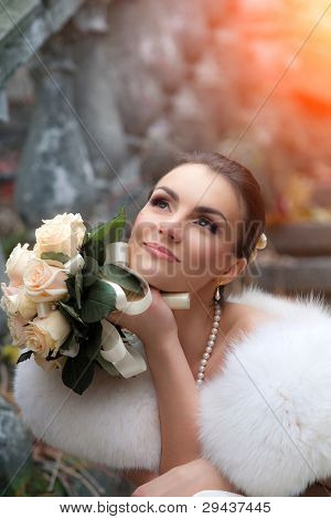 Beautiful young bride sitting on the stair.