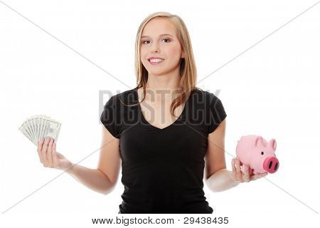 Happy teen holding a piggy bank and dollars, isolated on white background