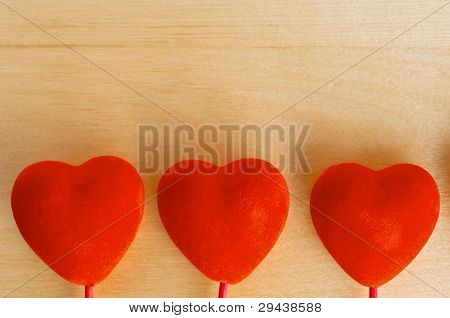 Three Hearts On Wood Background