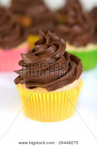cupcake with swirled chocolate frosting in yellow wrapper