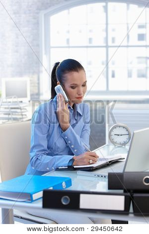 Businesswoman taking mobile phone call and writing notes into calendar at office desk.?