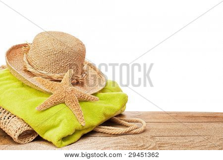 Beach bag and towel on sandy decking with white copyspace