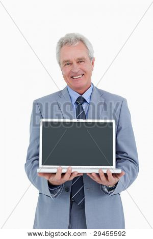 Smiling mature tradesman presenting screen of his laptop against a white background