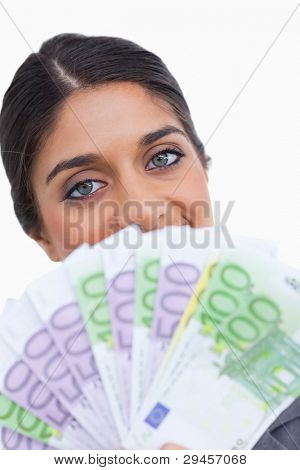 Close up of female entrepreneur hiding her face behind bank notes against a white background