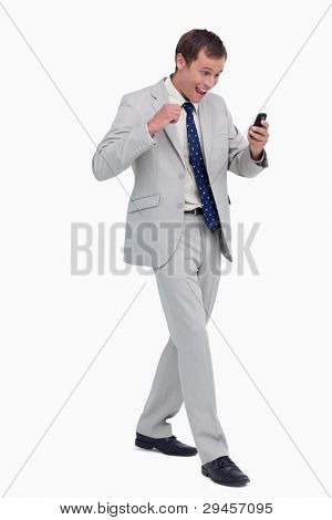 Happy businessman getting good news via text message against a white background