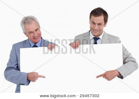 Smiling tradesmen pointing at blank sign in their hands against a white background