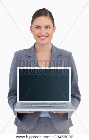 Smiling tradeswoman presenting screen of her laptop against a white background