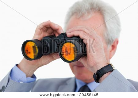 Close up of tradesman looking through binoculars against a white background