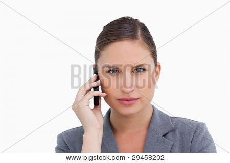 Close up of tradeswoman listening to caller against a white background