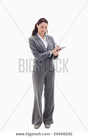 Businesswoman writing on a clipboard against white background