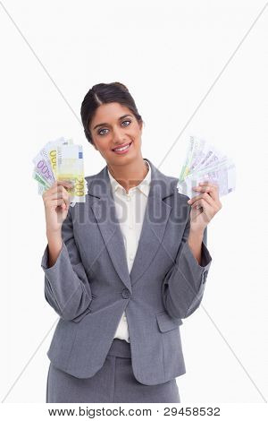 Smiling female entrepreneur holding bank notes against a white background