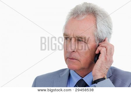 Close up of mature tradesman listening to caller against a white background