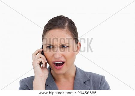 Close up of angry tradeswoman yelling at caller against a white background