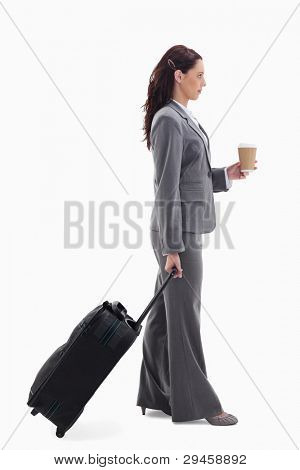 Profile of a businesswoman with a suitcase and holding a coffee against white background