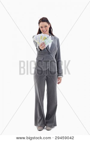 Happy businesswoman with a lot of bank notes in her hand against white background