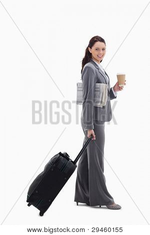 Profile of a businesswoman smiling with a suitcase, a newspaper and a coffee against white background