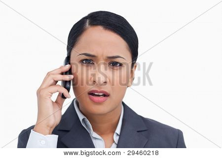 Close up of saleswoman getting bad news from caller against a white background