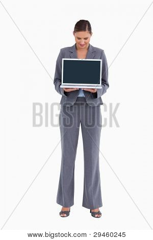 Tradeswoman presenting and looking at laptop screen against a white background
