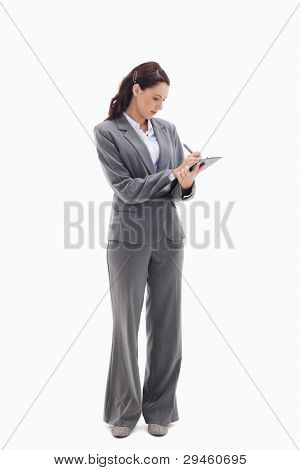 Businesswoman focusing and writing on a clipboard against white background