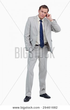 Businessman listening to caller on his mobile phone against a white background