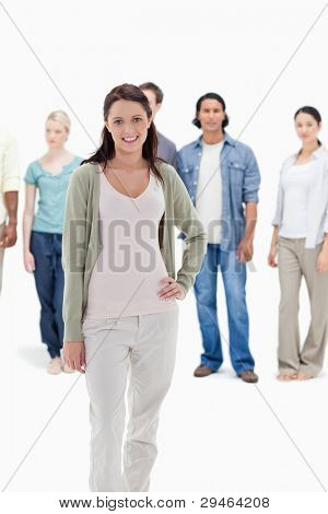 Close-up of people behind a smiling woman with her hand on her hip against white background