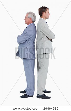 Side view of serious tradesmen standing back to back against a white background