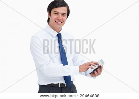 Side view of smiling tradesman with his tablet computer against a white background
