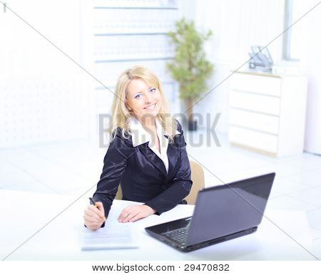 Portrait of a beautiful business woman working on her laptop in an office environment