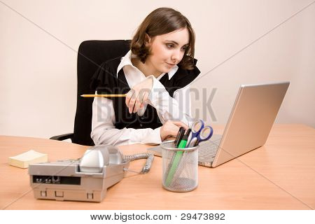 Young Secretary With Telephone, Laptop And Pencil Thinking