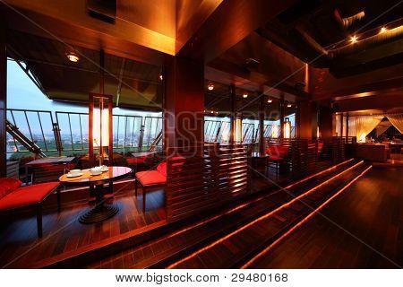 Reihe von Tischen und rot sitzen mit Partition Mauern in leere gemütliches Restaurant am Abend