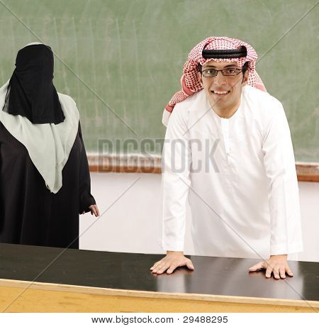 Smiling young success man, arabic traditional clothes, education and fashion concept, indoor, school or university, student or teacher.